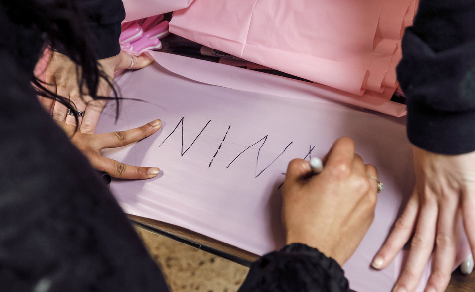 Photo - A supporter signs a pink ribbon during the University of Central Oklahoma