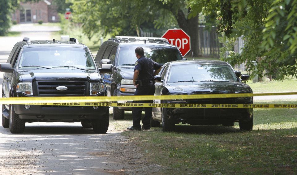 Crime tape marks the area where two men were shot to death in the 100 block of W Fourth Street in Arcadia Friday. Photo By Steve Gooch, The Oklahoman <strong>Steve Gooch - The Oklahoman</strong>