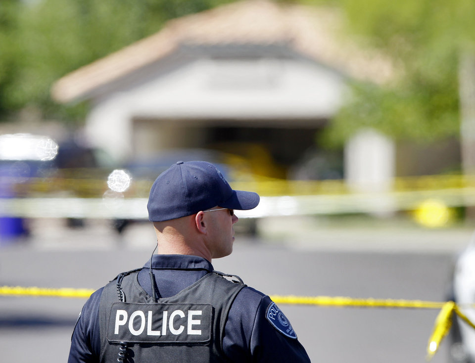 Photo -   A Gilbert police officer stands outside the police tape outside a crime scene Wednesday, May 2, 2012 in Gilbert, Ariz. Police in the Phoenix suburb of Gilbert say a man shot and killed four people, including a toddler, before killing himself. (AP Photo/Matt York)