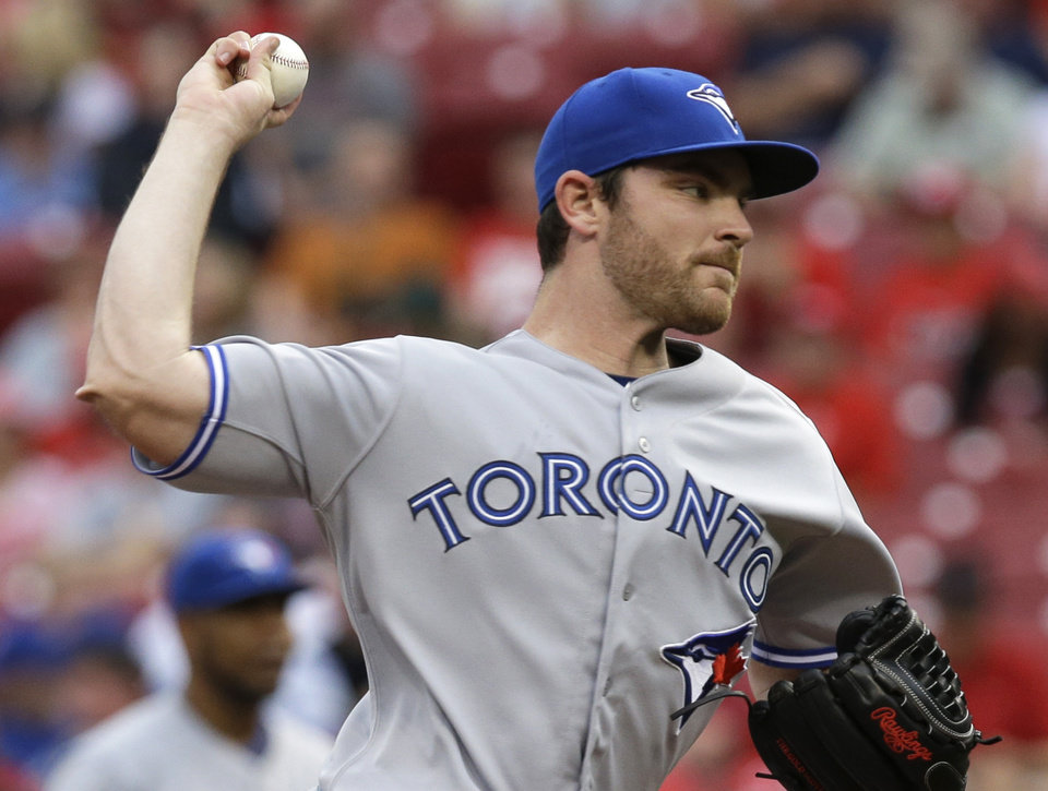 Photo - Toronto Blue Jays starting pitcher Liam Hendriks throws against the Cincinnati Reds in the first inning of a baseball game, Friday, June 20, 2014, in Cincinnati. (AP Photo/Al Behrman)