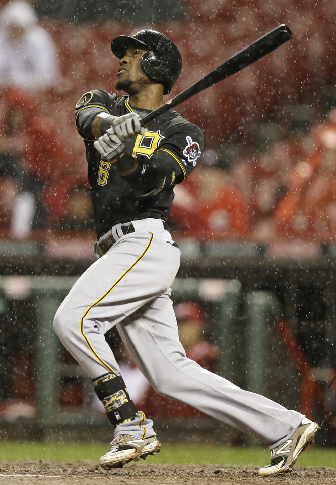 Photo - Pittsburgh Pirates' Starling Marte hits a solo home run off Cincinnati Reds starting pitcher Homer Bailey in the fifth inning of a baseball game, Monday, April 14, 2014, in Cincinnati. (AP Photo/Al Behrman)