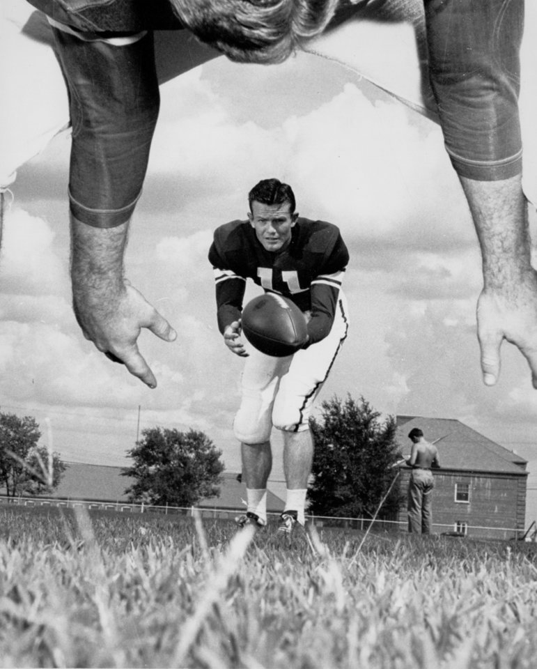 Photo - Ever wonder how it looks from the other side of the line?  Well, here's a defensive lineman's view of Darrell Royal, University of Oklahoma quarterback and punter, about to let fly with a 40-yard boot in 1948. The center is Charley Dowell. OKLAHOMAN ARCHIVE PHOTO