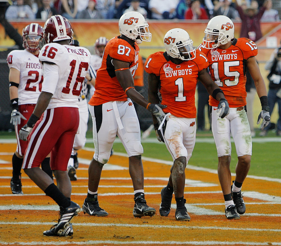 Photo - Oklahoma State's Brandon Pettigrew (87), Dez Bryant (1) and Seth Newton (15) walk off the field after Bryant's touchdown in the first half during the Insight Bowl college football game between Oklahoma State University (OSU) and the Indiana University Hoosiers (IU) at Sun Devil Stadium on Monday, Dec. 31, 2007, in Tempe, Ariz. 