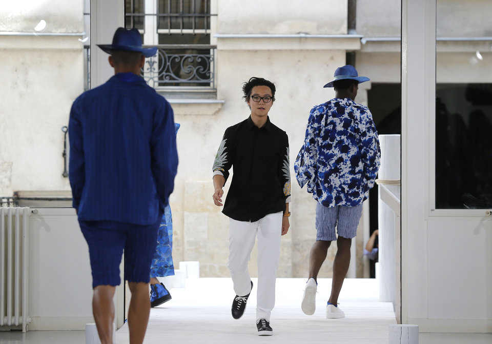 Photo - Japanese fashion designer Yusuke Takahashi acknowledges applause after the presentation of Issey Miyake's men's spring-summer 2015 fashion collection in Paris, France, Thursday, June 26, 2014. (AP Photo/Jacques Brinon)