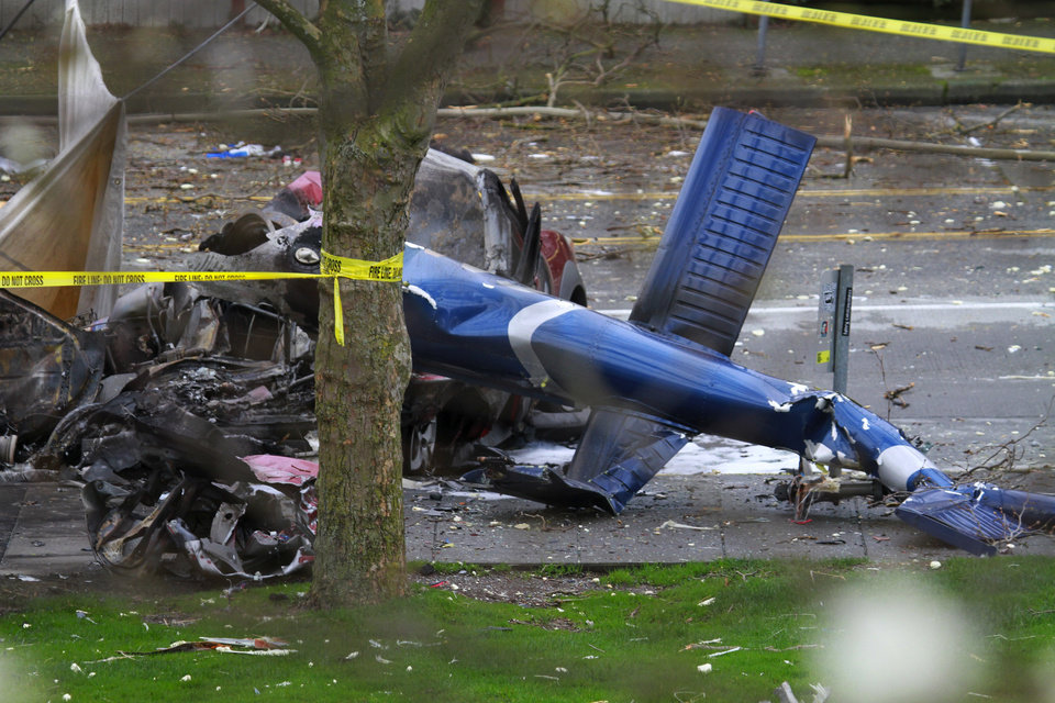 Photo - A piece of the wreckage of a news helicopter sits on a city street after crashing Tuesday, March 18, 2014, in Seattle.  A KOMO-TV helicopter crashed into a city street near Seattle's Space Needle, killing two people and critically injuring a person in a car on the ground. (AP Photo/The Seattle Times, Ken Lambert) OUTS: SEATTLE OUT, USA TODAY OUT, MAGAZINES OUT, TELEVISION OUT, SALES OUT. MANDATORY CREDIT TO BOTH THE SEATTLE TIMES AND THE PHOTOGRAPHER