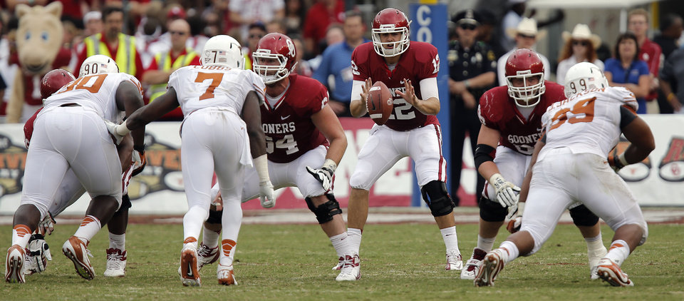 Photo - OU's Landry Jones (12) is snapped the ball during the Red River Rivalry college football game between the University of Oklahoma (OU) and the University of Texas (UT) at the Cotton Bowl in Dallas, Saturday, Oct. 13, 2012. Photo by Chris Landsberger, The Oklahoman