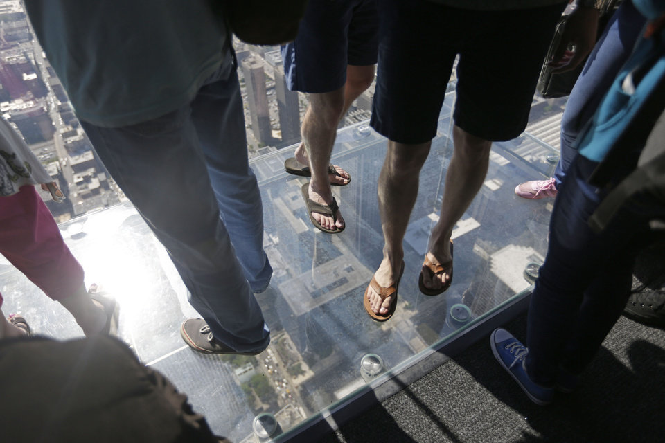 Photo - People stand on the floor of one of four transparent ledges that jut out from the 103rd floor of the Willis Tower in Chicago on Thursday, May 29, 2014. The see-through glass bays known as The Ledge were designed with a protective coating that completely covers all glass surfaces to protect against scratches. One of the coatings cracked Wednesday night when a family was standing on it. Officials say the family wasn't in danger and the coating does not affect the structural integrity of the enclosure. (AP Photo/M. Spencer Green)