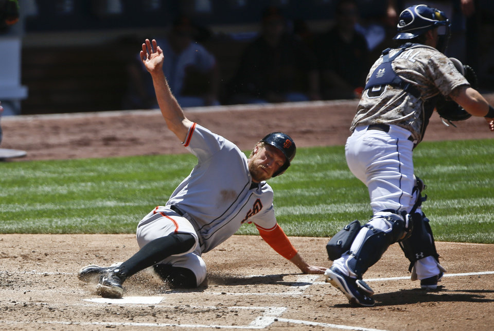 Photo - San Francisco Giants' Hunter Pence slides past San Diego Padres catcher Yasmani Grandal while scoring in the third inning of a baseball game Sunday, July 6, 2014, in San Diego.  Pence scored on a double by Joe Panik.   (AP Photo/Lenny Ignelzi)