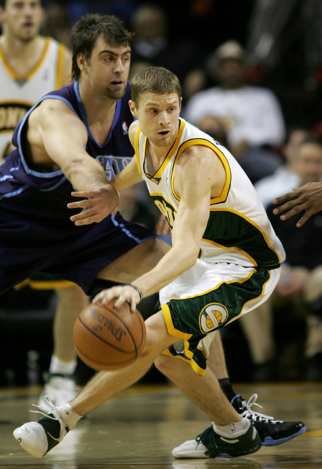 Photo - Seattle SuperSonics' Luke Ridnour, right, dribbles away from Utah Jazz's Mehmet Okur, of Turkey, in the first quarter of an NBA basketball game, in Seattle, Wednesday, Feb. 13, 2008.  Utah won 112-93. (AP Photo/Kevin P. Casey) ORG XMIT: WAKC109