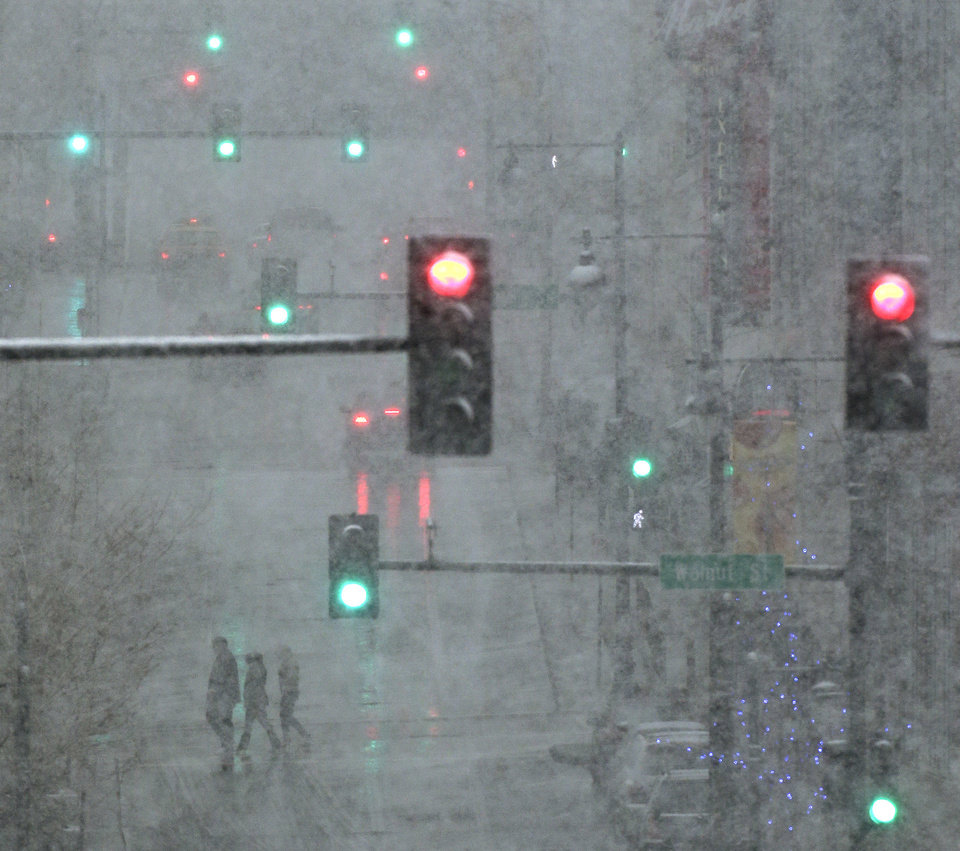 Photo - Pedestrians are shrouded in heavy snow as they cross a downtown street on Saturday, March 23, 2013, in Kansas City, Mo.  A winter storm warning is in effect for the area. (AP Photo/Charlie Riedel)