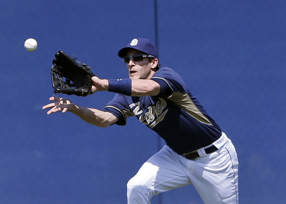 Photo - San Diego Padres' Chris Denorfia makes a running catch to deny a hit to Cleveland Indians' Lonnie Chisenhall in the third inning of a spring training exhibition baseball game, Saturday, March 29, 2014, in San Diego. (AP Photo/Lenny Ignelzi)