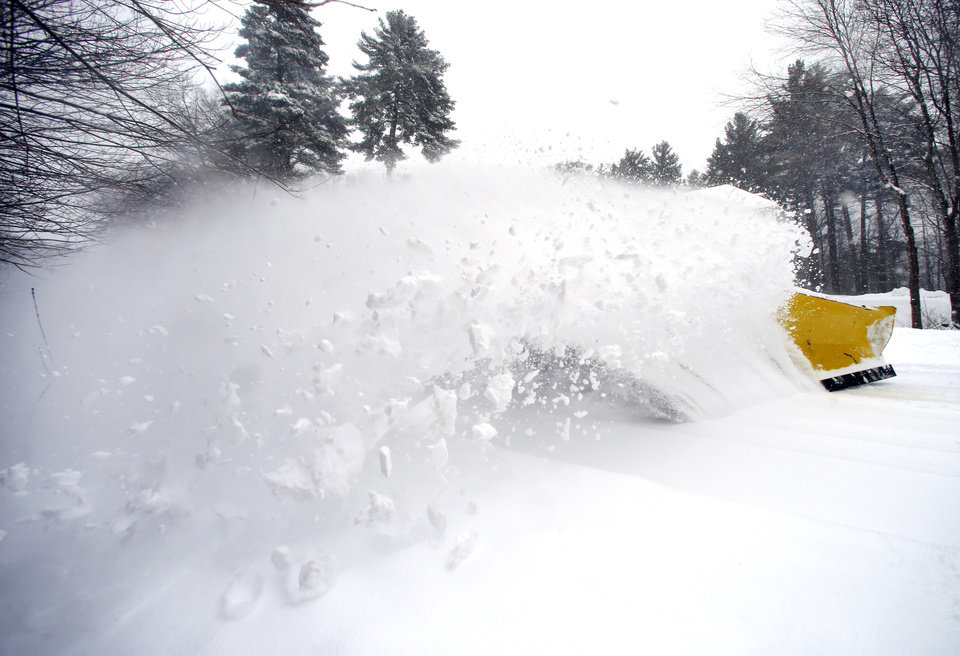 Photo - A wave of snow is kicked up as a snowplow truck clears a street in North Andover, Mass. Wednesday, Feb. 5, 2014. A foot of snow or more is predicted to fall in parts of Massachusetts. (AP Photo/Elise Amendola)