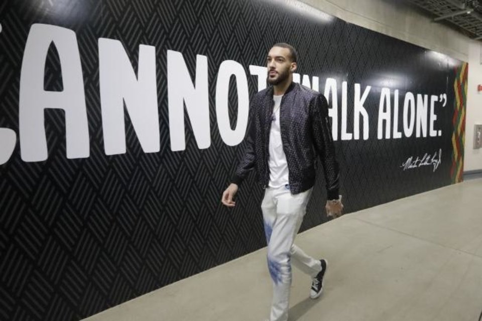 Photo -  Utah big man Rudy Gobert was cavalier about the likelihood he'd get coronavirus much less spread the disease. He was like a lot of us. Then, he tested positive — and became an accidental hero in the fight against the deadly disease. [AP Photo/Rick Bowmer]