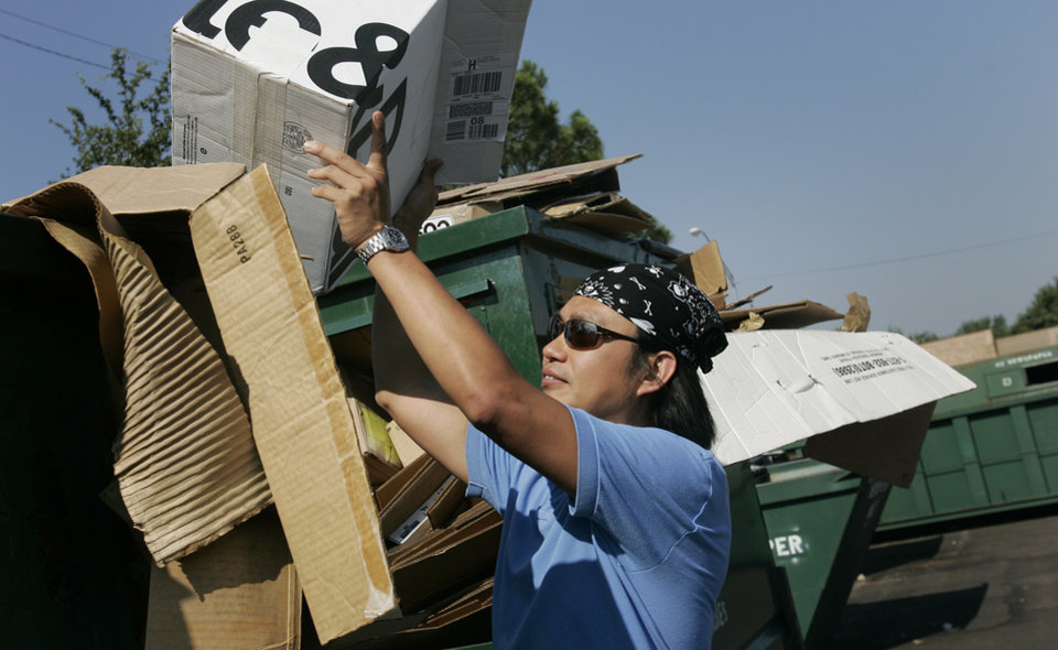 Tian Yu of Norman places a box in the cardboard recycling container at the Recycling Center at the  Cleveland County Fairgrounds Saturday, Aug. 2, 2008 in Norman, Ok. BY JACONNA AGUIRRE, THE OKLAHOMAN