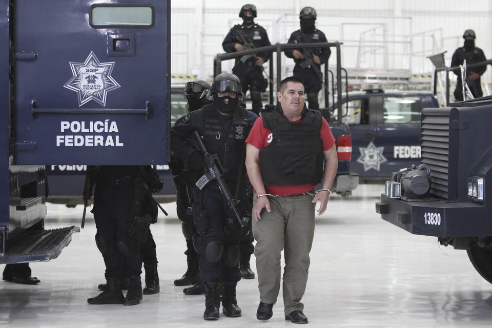 "Federal police officers escort Jose de Jesus Mendez Vargas, aka, ""El Chango"" or ""The Monkey,"" alleged leader of Mexican La Familia drug cartel, during his presentation to the press in Mexico City, Wednesday, June 22, 2011. Mendez was arrested at a federal police checkpoint in the Mexican central state of Aguascalientes Tuesday, without confrontation or casualties according to authorities. The government had offered a $2.5 million reward for his capture. (AP Photo/Miguel Tovar)"
