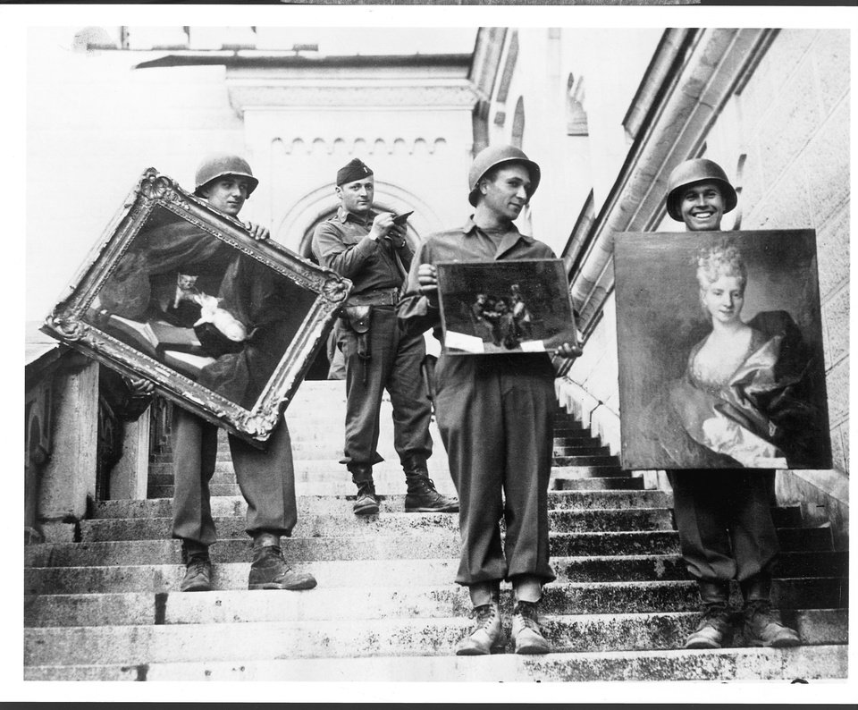 Photo - This photo provided by The Monuments Men Foundation for the Preservation of Art of Dallas, shows Monuments Man James Rorimer, with notepad, as he supervises American GI's hand-carrying paintings down the steps of the castle in Neuschwanstein, Germany in May of 1945. From a fairy tale-inspiring castle in the Bavarian Alps to a serene sculpture of Mary and Jesus by Michelangelo tucked away in a church in Belgium, sites and works of art across Europe can give travelers a glimpse at the heroic work done by those who worked to save cultural treasures during World War II.(AP Photo/National Archives and Records Administration)