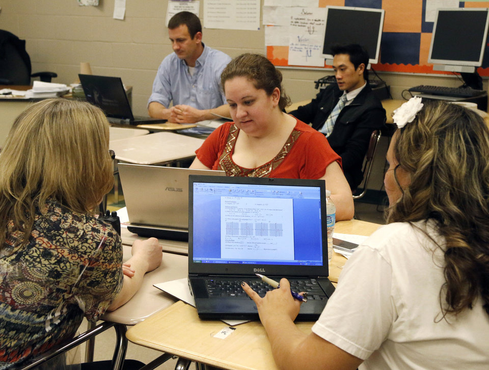 Photo - High school math teachers and administrators work together in professional learning communities at U.S. Grant High School in Oklahoma City on Monday. Foreground from left are Jennifer Kleyn, Sarah McKim, and Maria Wartchow. In the background are Kurtis Goodwin and Lam Pham.  PAUL HELLSTERN - The Oklahoman
