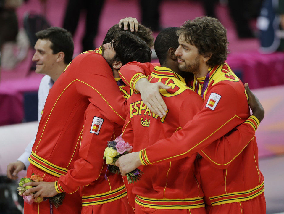 Spain\'s Pau Gasol, right, greets teammates following a ceremony at the 2012 Summer Olympics, Sunday, Aug. 12, 2012, in London. Spain won the silver medal. (AP Photo/Matt Slocum)