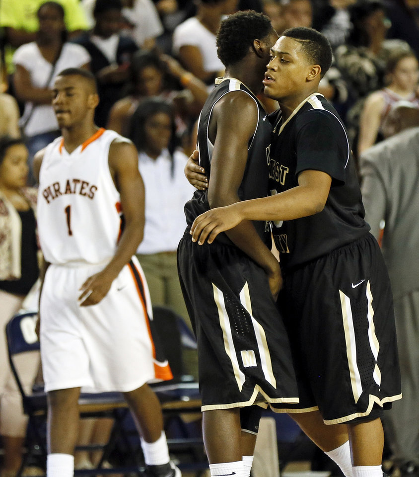 Midwest City's Cornell Neal, right, hugs Louis Parker (33) as Putnam City's Gerrell Murry (1) leaves the court after a Class 6A boys high school basketball game in the semifinals of the state tournament at the Mabee Center in Tulsa, Okla., Friday, March 8, 2013. Midwest City beat Putnam City, 57-50. Photo by Nate Billings, The Oklahoman