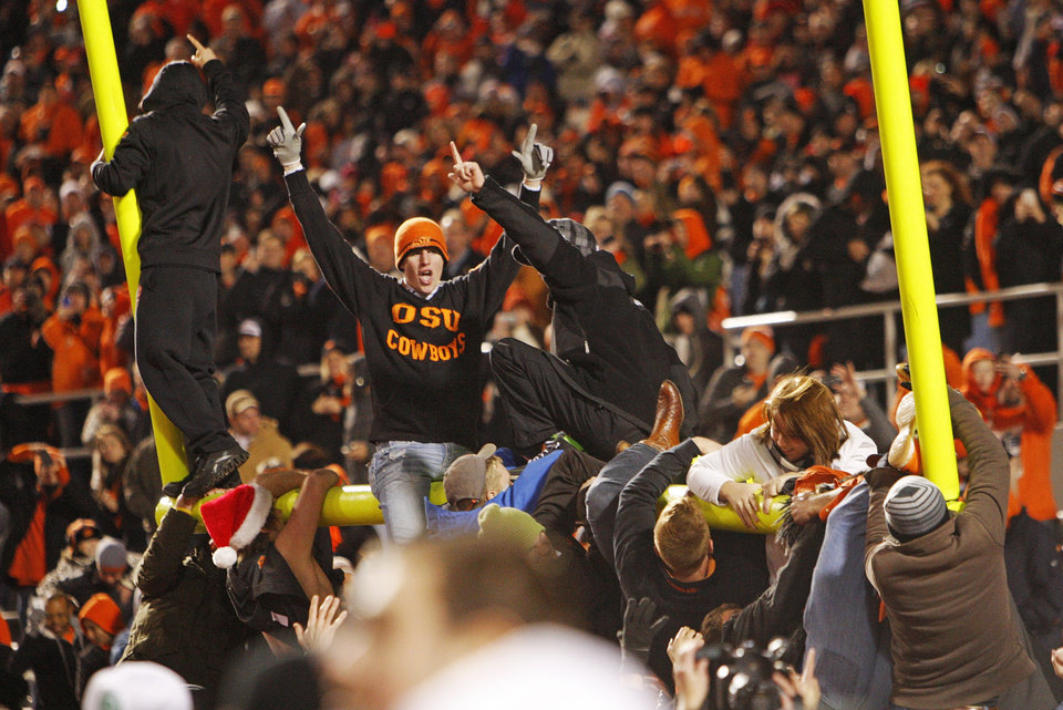 Photo - OSU fans tear down the goal in the west end zone as they celebrate after the Bedlam college football game between the Oklahoma State University Cowboys and the University of Oklahoma Sooners at Boone Pickens Stadium in Stillwater, Okla., Saturday, Dec. 3, 2011. OSU beat OU, 44-10. Photo by Nate Billings, The Oklahoman