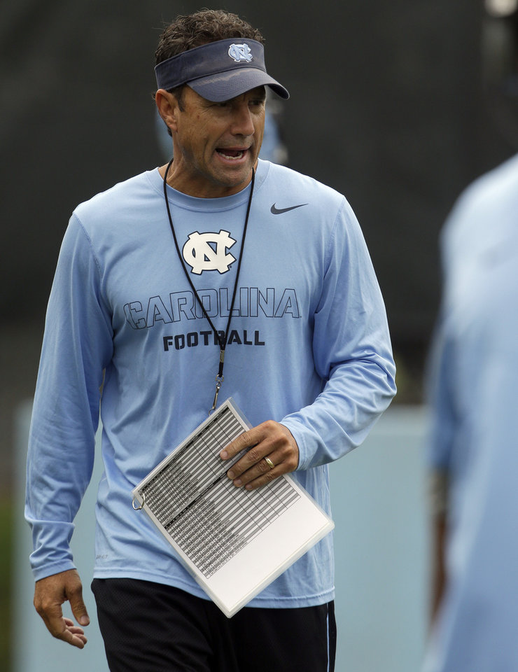 Photo - In this photo taken Friday, Aug. 1, 2014, North Carolina coach Larry Fedora directs his team during an NCAA football practice in Chapel Hill, N.C. (AP Photo/Gerry Broome)