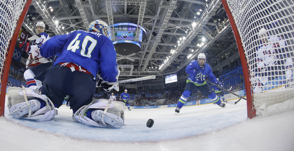 Photo - USA forward Phil Kessel, right, watches as his third goal sails past Slovenia goaltender Luka Gracnar during the third period of a men's ice hockey game at the 2014 Winter Olympics, Sunday, Feb. 16, 2014, in Sochi, Russia. (AP Photo/Matt Slocum, Pool)