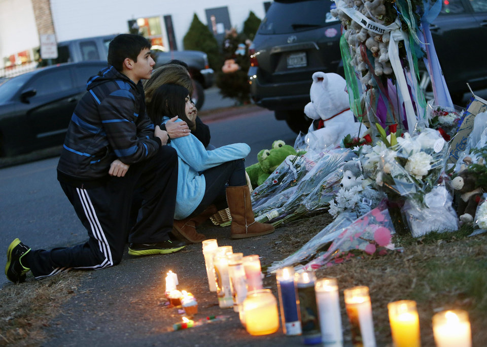 Photo - Mourners pay their respects at a memorial for shooting victims near Sandy Hook Elementary School, Saturday, Dec. 15, 2012 in Newtown, Conn.  A gunman walked into Sandy Hook Elementary School in Newtown Friday and opened fire, killing 26 people, including 20 children. (AP Photo/Jason DeCrow) ORG XMIT: CTJD118