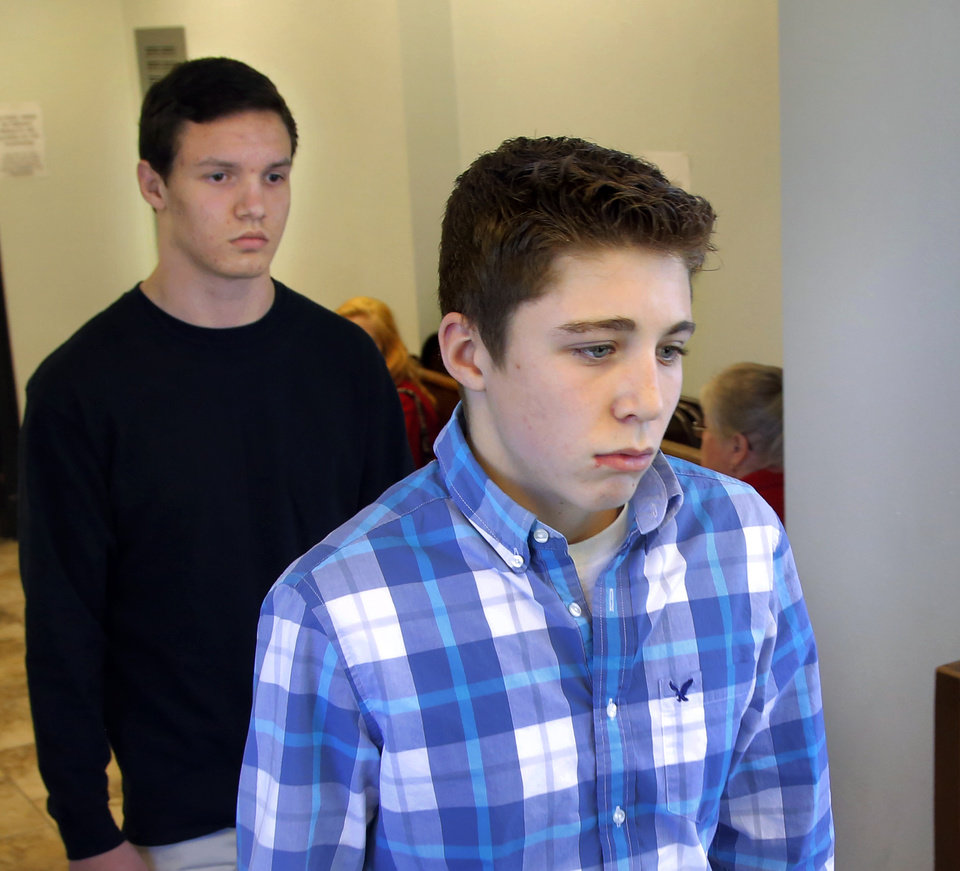 Photo - Hunter Oren Matthews, 17, front, and Chase Denton Smith, 16, are led to the elevator after entering pleas of not guilty to charges of rape by instrumentation. Four students from Norman North High School were arraigned before Special Judge Trisha  Misak in the Garvin County Courthouse in downtown Pauls Valley Tuesday afternoon, Feb. 2, 2016. Photo by Jim Beckel, The Oklahoman.