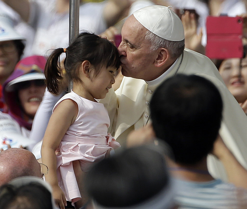 Photo - Pope Francis, right, kisses a girl as he arrives with the popemobile to celebrate a mass and the beatification Paul Yun ji-Chung and 123 martyr companions at Gwanghwamun Gate in Seoul, South Korea, Saturday, Aug. 16, 2014. Paul Yun Ji-Chung, born in 1759,  was among the earliest Catholics on the Korean Peninsula. (AP Photo/Gregorio Borgia)