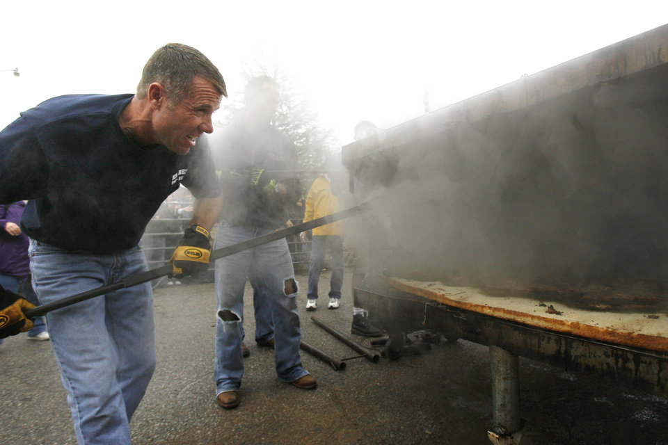 Photo - El Reno Fire Chief Kent Lagaly peers through the smoke as he and other city workers prepare a huge onion fried burger during El Reno's Burger Day Festival in downtown El Reno, OK, Saturday, May 2, 2009. BY PAUL HELLSTERN, THE OKLAHOMAN