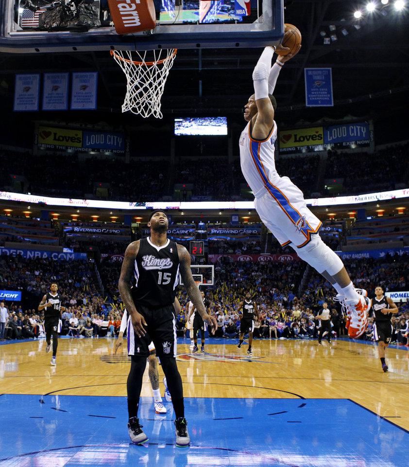 Photo - Oklahoma City's Russell Westbrook (0) goes up for a dunk as Sacramento's DeMarcus Cousins (15) watches during an NBA game between the Oklahoma City Thunder and the Sacramento Kings at Chesapeake Energy Arena in Oklahoma City, Friday, March 28, 2014. Oklahoma City on 94-81. PHOTO BY BRYAN TERRY, The Oklahoman