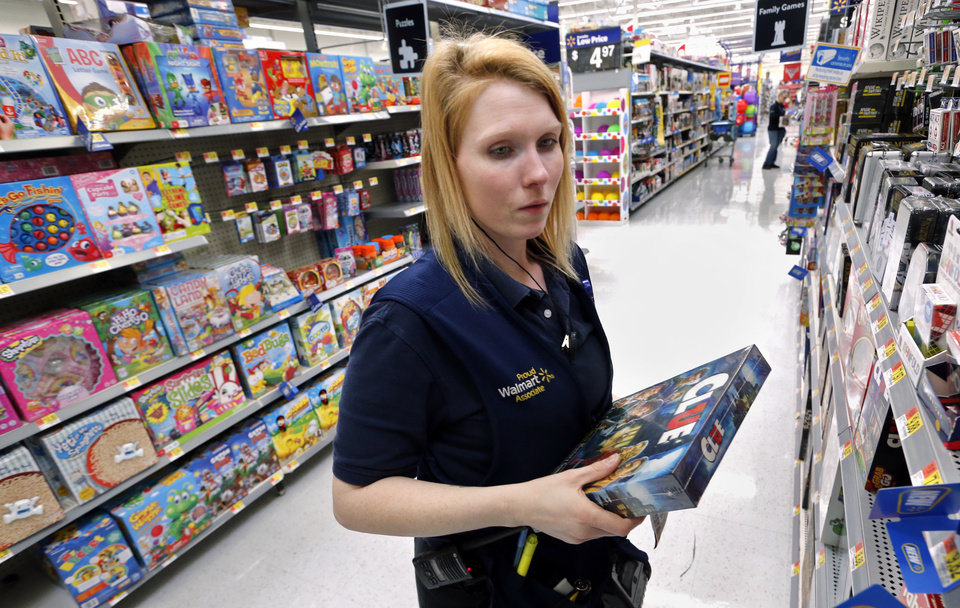 Photo -  Department manager Amber Compton restocks items at the Belle Isle Walmart on Tuesday. [Photo by Steve Sisney, The Oklahoman]