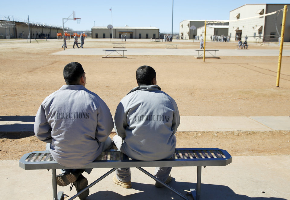 Photo -  Inmates sit on a bench in the yard at the Bill Johnson Correctional Center. [Photo by Nate Billings, The Oklahoman]