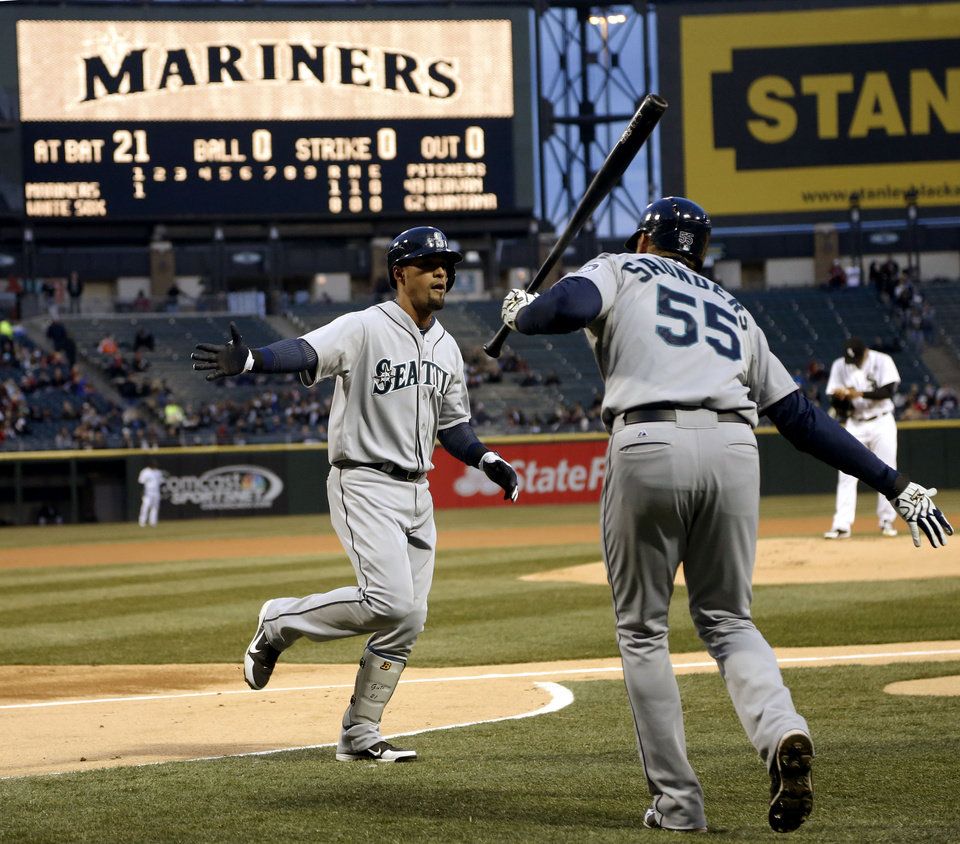 Seattle Mariners' Michael Saunders (55) greets teammate Franklin Gutierrez outside the dugout after Gutierrez's lead-off home run off Chicago White Sox starting pitcher Jose Quintana during the first inning of a baseball game on Friday, April 5, 2013, in Chicago. (AP Photo/Charles Rex Arbogast)