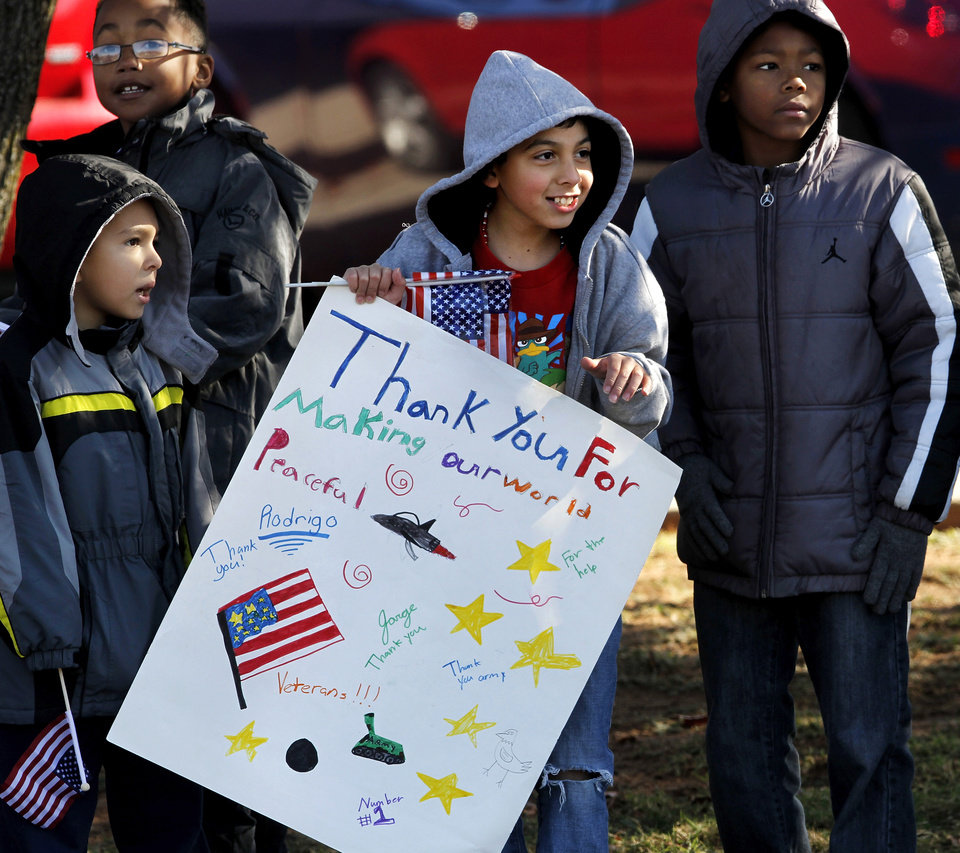 Photo - Students from Soldier Creek Elementary School carry flags and hold signs as parade moves past their school at SE 15 and Douglas. The city of Midwest City teamed with civic leaders and local merchants to display their appreciation for veterans and active military forces by staging a hour-long Veteran's Day parade that stretched more than a mile and a half along three of the city's busiest streets Monday morning, Nov. 12, 2012. Hundreds of people lined the parade route, many of them waving small American flags that had ben distributed by volunteers who marched near the front of the parade. A fly-over performed by F-16s from the138th Fighter Wing, Oklahoma Air National Guard unit in Tulsa thrilled spectators. Five veterans representing military personnel who served in five wars and military actions served as  Grand Marshals for the parade. Leading the parade was the Naval Reserve seven-story American flag, carried by 100 volunteers from First National Bank of Midwest City, Advantage Bank and the Tinker Federal Credit Union. The flag is 50 feet by 76 feet, weighs 110 pounds and was sponsored by the MWC Chapter of Disabled American Veterans. Photo by Jim Beckel, The Oklahoman