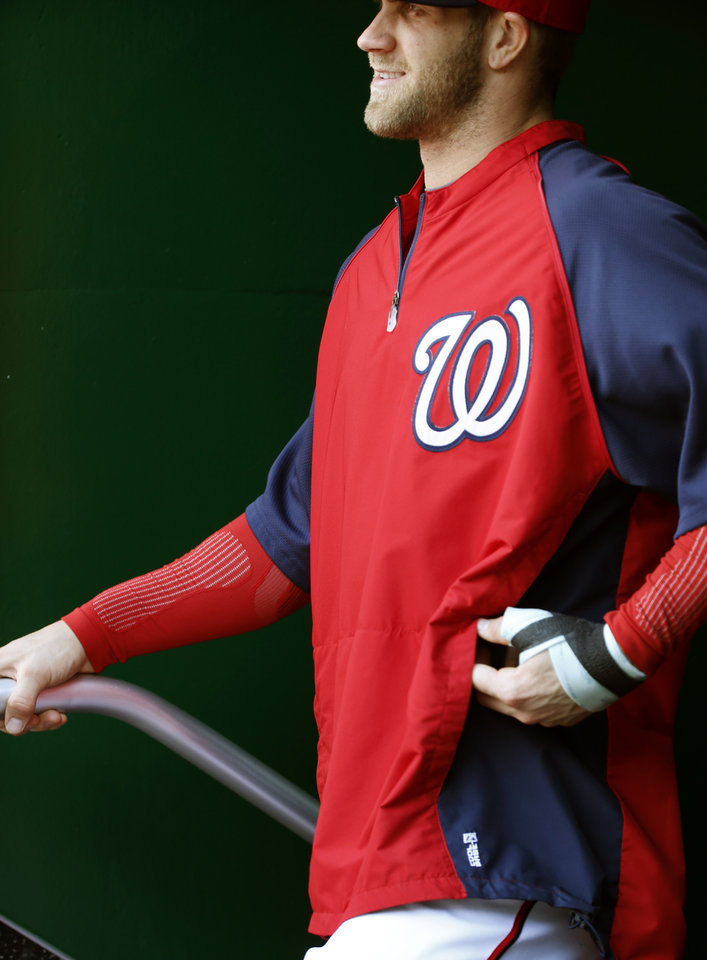Photo - CORRECTS TO LEFT HAND, NOT RIGHT - Washington Nationals left fielder Bryce Harper stands in the dugout with a bandage on his left hand during the fifth inning of a baseball game against the San Diego Padres at Nationals Park Saturday, April 26, 2014, in Washington. Harper injured the hand Friday and is not in the lineup Saturday. (AP Photo/Alex Brandon)