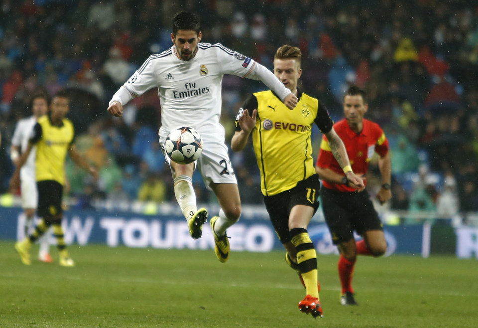 Photo - Real's Isco, left, is followed by Dortmund's Marco Reus during a Champions League quarterfinal first leg soccer match between Real Madrid and Borussia Dortmund at the Santiago Bernabeu   stadium in Madrid, Spain, Wednesday, April 2, 2014. (AP Photo/Andres Kudacki)