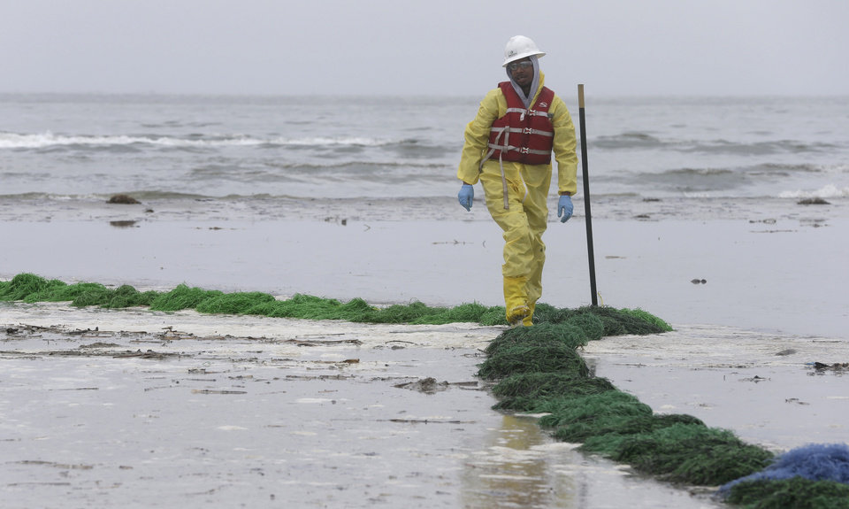 Photo - A worker checks a viscous snare line along East Beach in Galveston, Texas, to clean up an oil spill Monday, March 24, 2014. Thousands  of gallons of tar-like oil spilled into the major U.S. shipping channel after a barge ran into a ship Saturday. (AP Photo/Pat Sullivan)