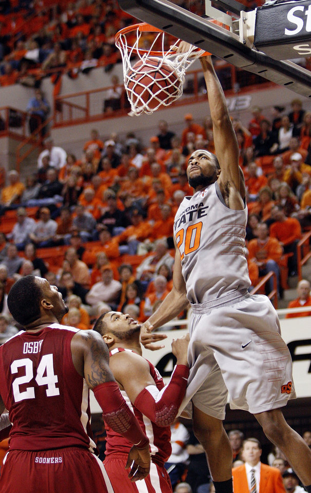 Photo - OSU's Michael Cobbins (20) dunks the ball in front of Romero Osby (24) and Barry Honore (31) of OU in the second half during the Bedlam men's college basketball game between the Oklahoma State University Cowboys and the University of Oklahoma Sooners at Gallagher-Iba Arena in Stillwater, Okla., Monday, Jan. 9, 2012. OSU beat OU, 72-65. Photo by Nate Billings, The Oklahoman