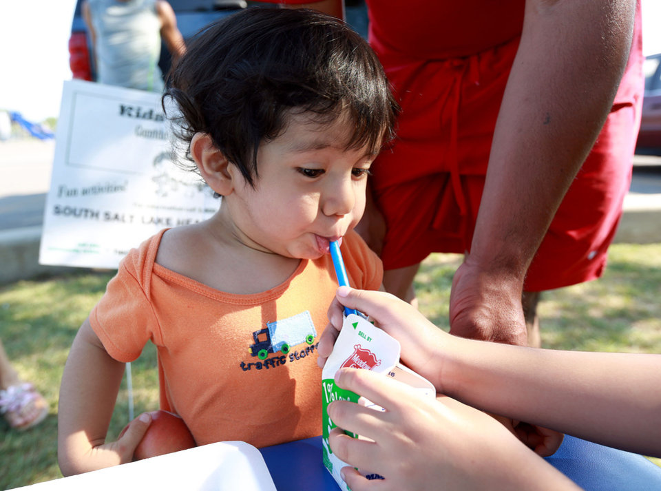 Photo -       Emanuel Perez sips on milk outside of the Central Park Community Center in South Salt Lake on Friday, July 18, 2014. His dinner is part of the Salt Lake CAP summer food program, which offers free dinner to children at five locations in the valley, Monday through Friday. The Perez family brought their own table and chairs for the children to eat on.