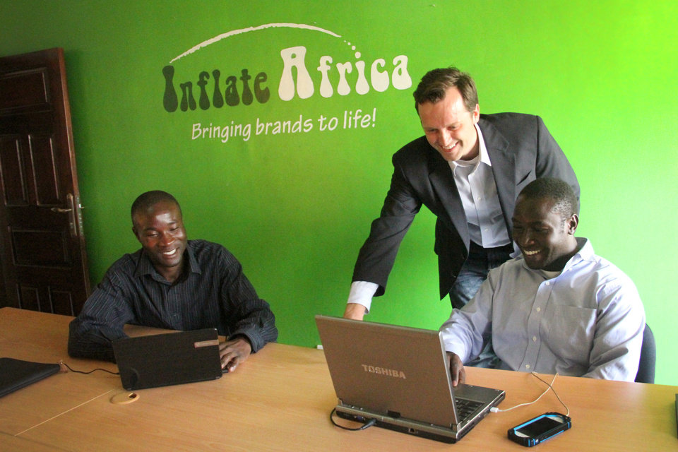 Photo -  Tyler Schooley meets with Francis and Willis, two of his employees at Inflate Africa, his advertising business based in Kampala, Uganda. Photo provided by Dani Walker Kreutter   Dani Walker Kreutter