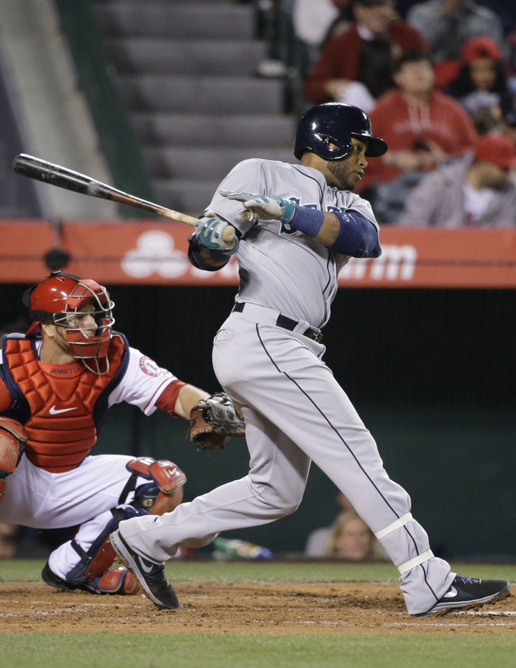 Photo - Seattle Mariners' Robinson Cano follows through on an RBI single during the third inning of a baseball game against the Los Angeles Angels on Wednesday, April 2, 2014, in Anaheim, Calif. (AP Photo/Jae C. Hong)
