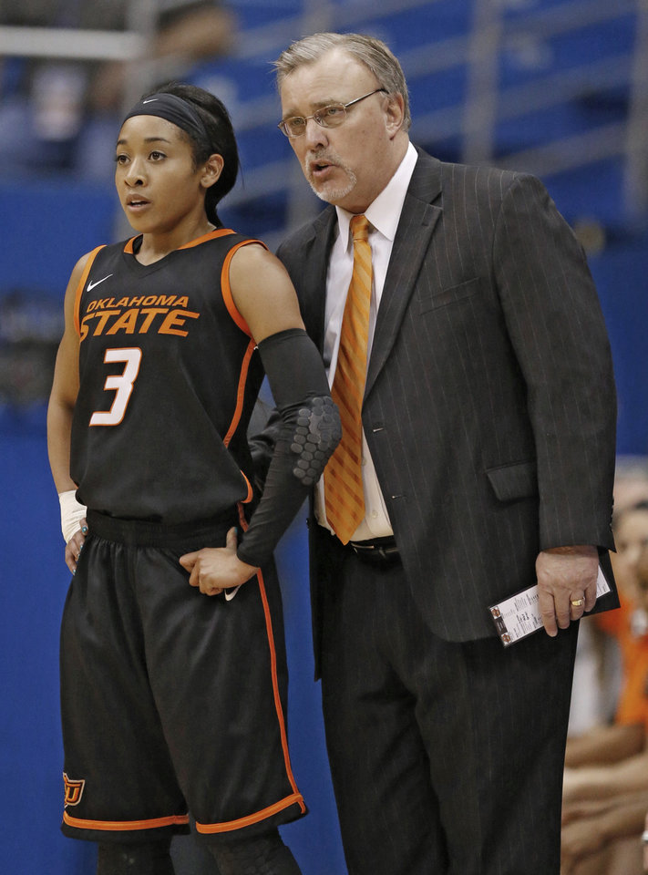 Photo - Oklahoma State head coach Jim Littell, right, talks with guard Tiffany Bias (3) during the first half of an NCAA college basketball game against Kansas in Lawrence, Kan., Wednesday, Jan. 22, 2014. (AP Photo/Orlin Wagner)