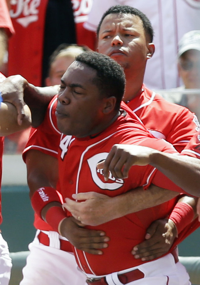 Photo - Cincinnati Reds' Aroldis Chapman (54) is held back during a bench clearing scuffle in the 10th inning of a baseball game against the Chicago Cubs, Thursday, July 10, 2014, in Cincinnati. Chicago won 6-4 in 12 innings. (AP Photo/Al Behrman)