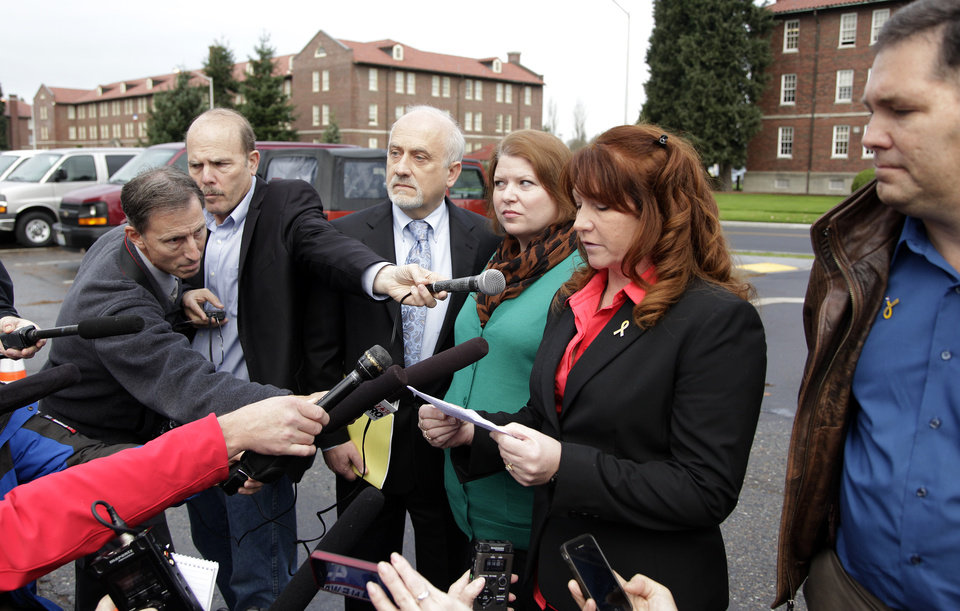 Photo -   Kari Bales, third from right, stands next to attorney Lance Rosen, third from left, as she listens to her sister, Stephanie Tandberg, second from right, read a statement to reporters Tuesday, Nov. 13, 2012, outside the building housing a military courtroom on Joint Base Lewis McChord in Washington state, where a preliminary hearing ended Tuesday for Kari's husband, U.S. Army Staff Sgt. Robert Bales. Bales is accused of 16 counts of premeditated murder and six counts of attempted murder for a pre-dawn attack on two villages in Kandahar Province in Afghanistan in March of 2012. At right is Stephanie's husband, Eric Tandberg. (AP Photo/Ted S. Warren)