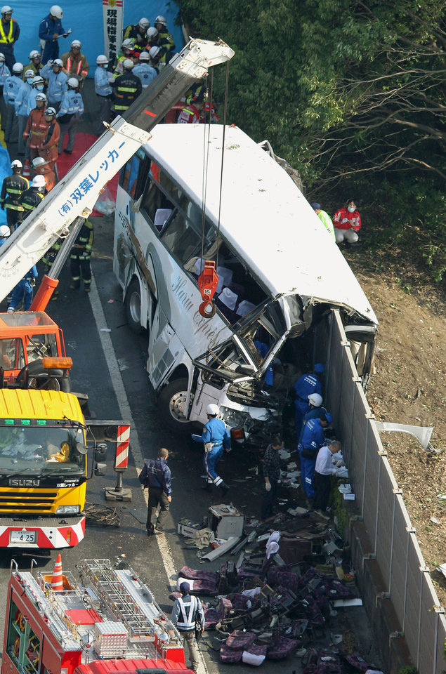 Photo -   Rescuers work near the wreckage of a destroyed bus on a highway in Fujioka, Gunma prefecture, north of Tokyo Sunday, April 29, 2012. Police say the bus carrying dozens of holiday makers crashed on the highway while heading for Tokyo Disneyland, killing at least seven people and injuring dozens. (AP Photo/Kyodo News) JAPAN OUT, MANDATORY CREDIT, NO LICENSING IN CHINA, HONG KONG, JAPAN, SOUTH KOREA AND FRANCE