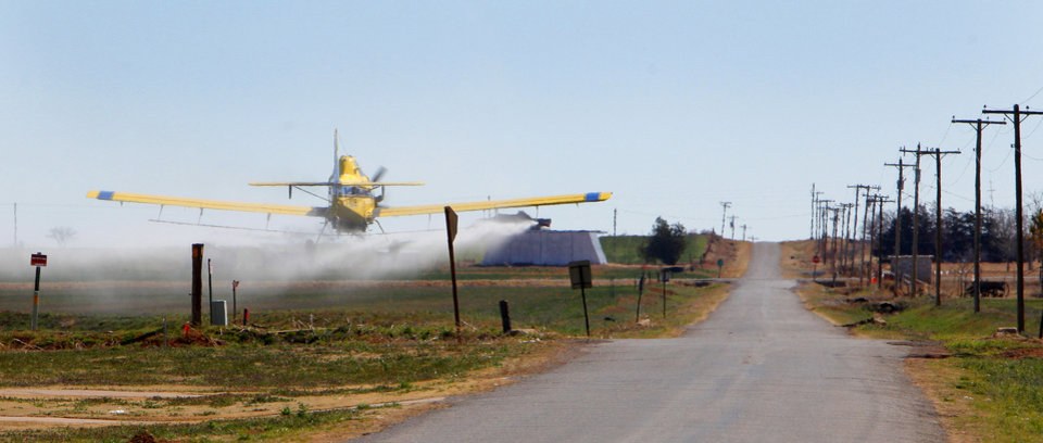 "Photo -  T.J. Beach, of Elmer, called an aerial sprayer to come take care of mites in a wheat field. ""A reason we have the mites is because it's dry,"" Beach said. Below, a sign beckons people to ""Pray for Rain.""    David McDaniel -"