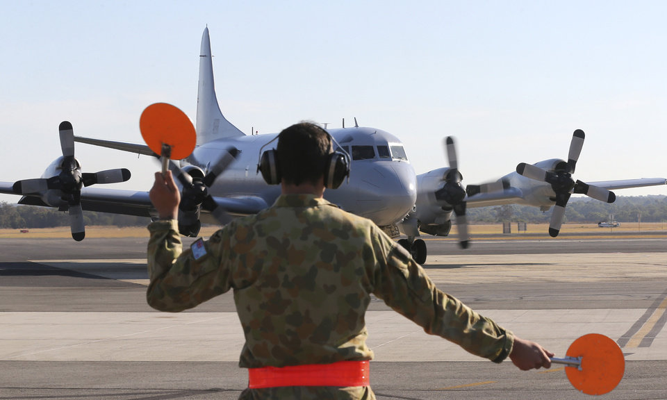 Photo - Royal Australian Air Force AP-3C Orion is guided by a ground crew man on the tarmac at RAAF Base Pearce following their search operation for the missing Malaysia Airlines Flight MH370 in Perth, Australia, Thursday, March 27, 2014. Planes and ships searching for debris suspected of being from the downed Malaysia Airlines jetliner failed to find any Thursday before bad weather cut their hunt short in a setback that came as Thailand said its satellite had spotted even more suspect objects. (AP Photo/Rob Griffith)