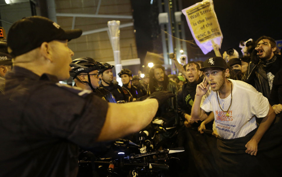Photo - Occupy Demonstrators speak to police after the demonstrators used a tarp to push against a police barricade during an unscheduled protest march, Tuesday, Sept. 4, 2012, in Charlotte, N.C. The Democratic National Convention begins today. (AP Photo/Patrick Semansky) ORG XMIT: XDNC159
