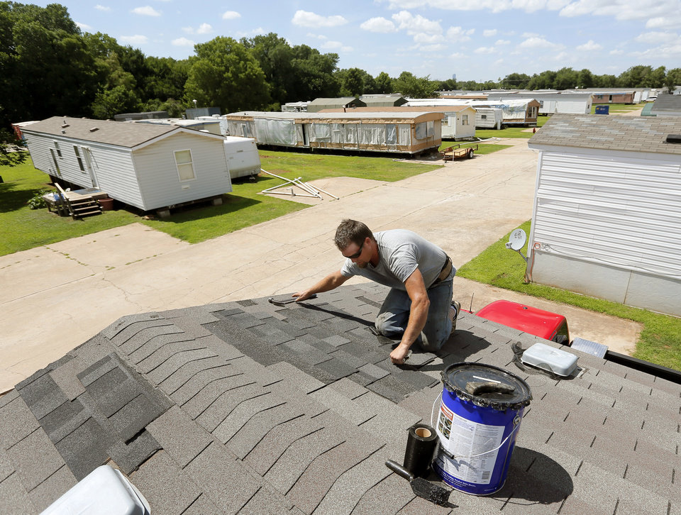 Photo -  David Arnold repairs the roof of a mobile home at Hand Up Ministries, 2130 SE 59. Arnold is a registered sex offender who has lived at Hand Up Ministries since April. He works as a handyman at the mobile home park. [Photo by Nate Billings, The Oklahoman]